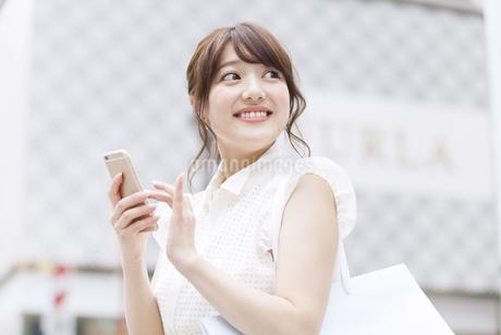 街中でスマートフォンを持ち微笑む女性の写真素材 [FYI00465747]