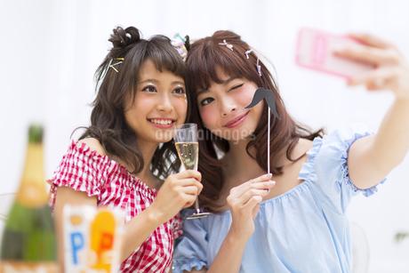 シャンパンとパーティーグッズを持ち写真を撮る女性2人の写真素材 [FYI00465759]