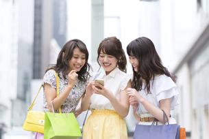 街中でスマートフォンを持ち笑う女性3人の写真素材 [FYI00465761]