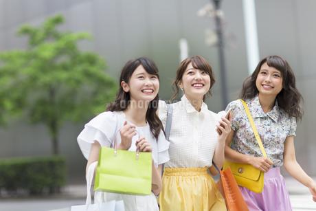 街中でスマートフォンを持ち微笑む女性3人の写真素材 [FYI00465762]