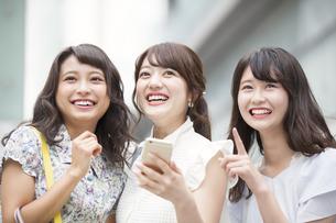 街中でスマートフォンを持ち笑う女性3人の写真素材 [FYI00465763]