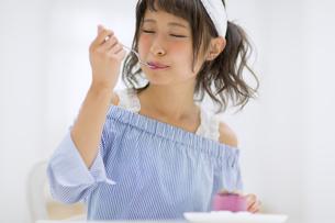 ケーキを食べて微笑む女性の写真素材 [FYI00465767]