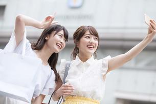 街中で写真を撮る女性2人の写真素材 [FYI00465768]