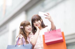 街中で写真を撮る女性2人の写真素材 [FYI00465771]