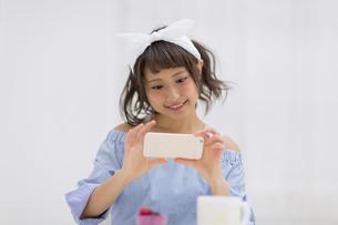 スマートフォンで写真を撮る女性の写真素材 [FYI00465772]