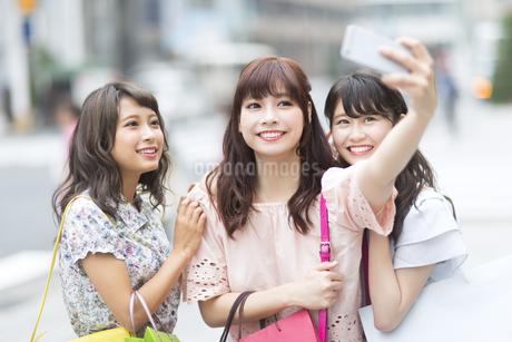 街中で写真を撮る女性3人の写真素材 [FYI00465774]
