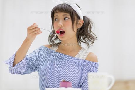 ケーキに乗っていたラズベリーを食べる女性の素材 [FYI00465780]