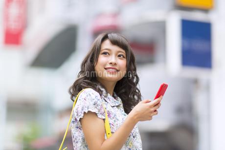 街中でスマートフォンを持ち微笑む女性の写真素材 [FYI00465782]