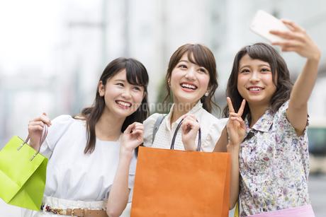 街中で写真を撮る女性3人の写真素材 [FYI00465784]