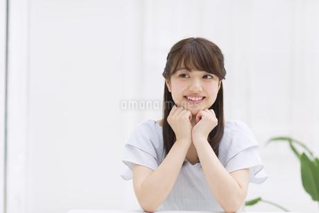 頬に両手を当てポーズをとる女性の写真素材 [FYI00465806]