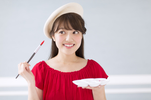 筆とパレットを持って微笑む女性の写真素材 [FYI00465813]