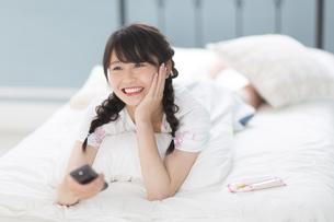 ベッドの上でリモコンを持って笑う女性の写真素材 [FYI00465820]
