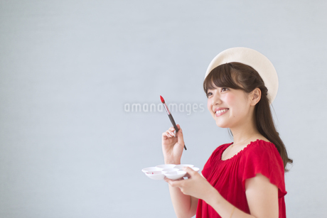 筆とパレットを持って微笑む女性の写真素材 [FYI00465822]