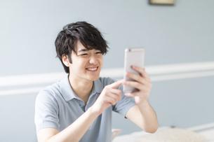 スマートフォンを見て笑う男性の写真素材 [FYI00465826]