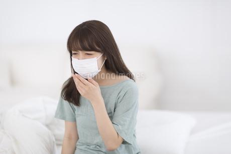 マスクをして咳き込む女性の素材 [FYI00465827]