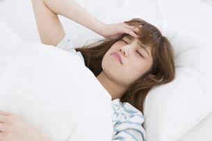 ベッドで頭痛に悩む女性の写真素材 [FYI00465829]