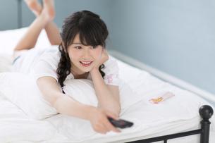 ベッドの上でリモコンを操作する女性の写真素材 [FYI00465833]