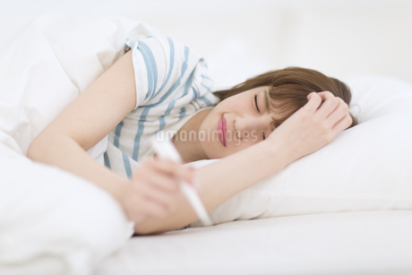 ベッドで体温計を持ち寝込む女性の素材 [FYI00465836]