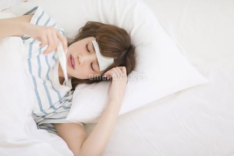 ベッドで体温計を見る女性の素材 [FYI00465844]