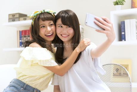 スマートフォンで写真を撮る女性2人の素材 [FYI00465851]