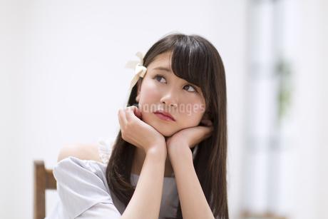 頬に両手を当て考え事をする女性の素材 [FYI00465853]