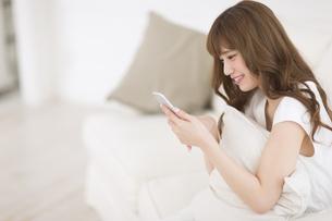 ソファーに座ってスマートフォンを見て微笑む女性の写真素材 [FYI00465855]
