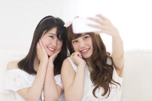 スマートフォンで写真を撮る女性2人の写真素材 [FYI00465859]