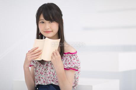本を持ち微笑む女性の素材 [FYI00465860]