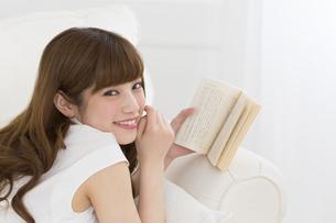 ソファーの上で本を持ち笑う女性の写真素材 [FYI00465862]
