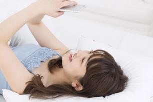 ベッドの上でスマートフォンを持ち笑う女性の写真素材 [FYI00465865]