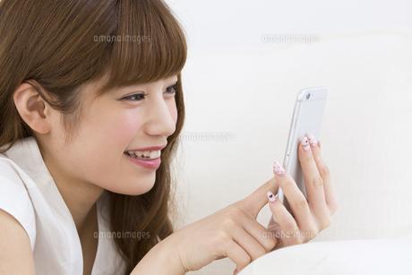 スマートフォンを見て笑う女性の写真素材 [FYI00465886]
