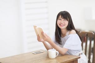 音楽を聞きながら本を持ち笑う女性の写真素材 [FYI00465889]