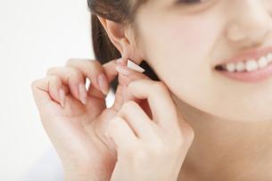 耳にピアスをつける女性の手元の写真素材 [FYI00465894]