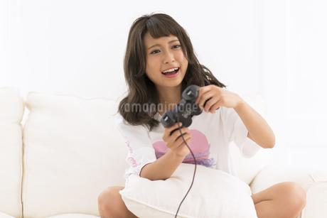 ソファーの上でゲームをする女性の写真素材 [FYI00465895]