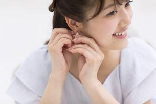 耳にピアスをつける女性の写真素材 [FYI00465908]