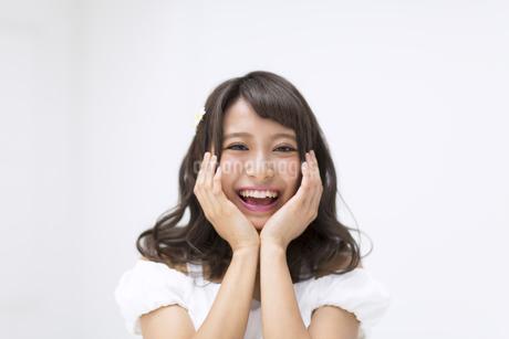頬に両手を当て笑う女性の写真素材 [FYI00465956]