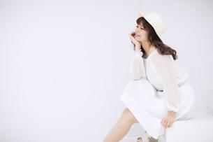 帽子を被り座って微笑む女性の写真素材 [FYI00465962]