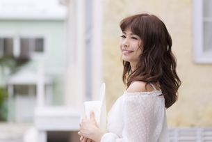 帽子を手に持ち微笑む女性の写真素材 [FYI00465977]