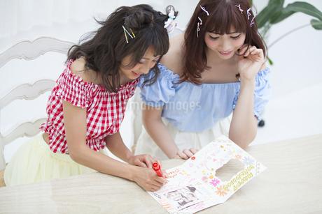 アルバムに文字を記入している女性2人の写真素材 [FYI00465993]