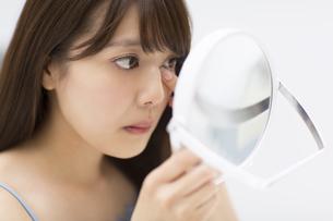 鏡で顔のチェックをする女性の写真素材 [FYI00466020]