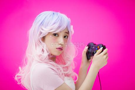 ゲームのコントローラー持つ女性の写真素材 [FYI00466031]