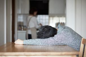 テーブルに倒れ込むミドル男性の写真素材 [FYI00466665]