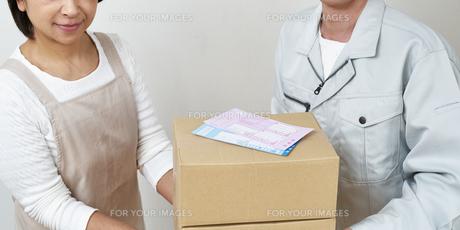 荷物を持つ宅配員と主婦の写真素材 [FYI00466668]