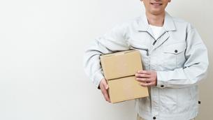 荷物を持つ作業着男性の写真素材 [FYI00466684]
