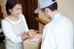 荷物を届ける宅配員の写真素材 [FYI00466717]