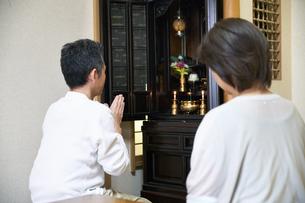 仏壇で拝む中年夫婦の写真素材 [FYI00466865]