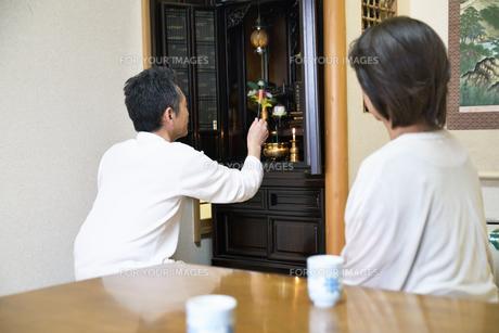 仏壇で拝む中年夫婦の写真素材 [FYI00466872]