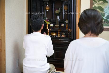 仏壇で拝む中年夫婦の写真素材 [FYI00466873]