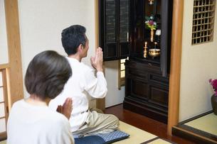 仏壇で拝む中年夫婦の写真素材 [FYI00466878]