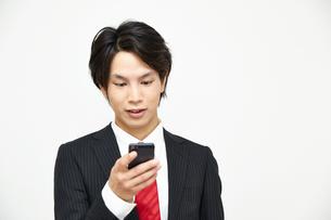 携帯電話を使うビジネスマンの写真素材 [FYI00466964]